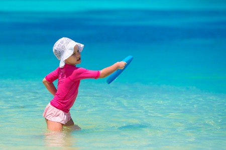 children swimsuit: Little girl playing with flying disc at white beach Stock Photo