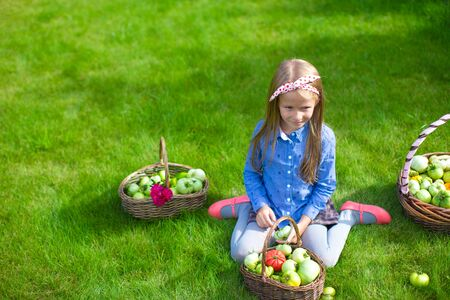 girl in full growth: Adorable little girl with autumn harvest of tomatoes in baskets