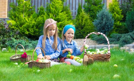 girl in full growth: Two little happy girls with great autumn harvest of tomatoes in baskets