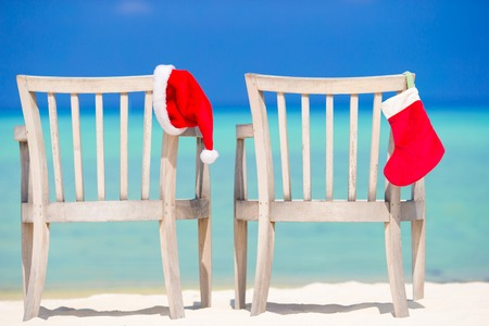 christmas stocking: Red Christmas stocking and Santa Hat on chair at tropical white beach
