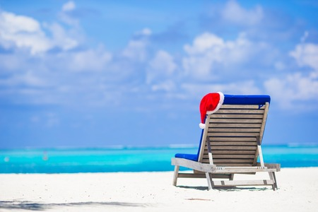 Sun chair lounge with red Santa Hat on tropical white beach and turquoise water Archivio Fotografico