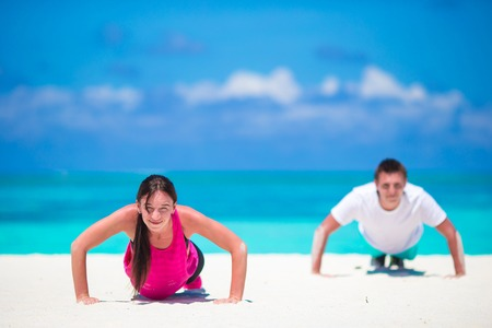 situp: Young fitness couple doing push-ups during outdoor cross training workout on tropical beach Stock Photo
