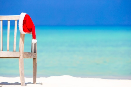 Red santa hat on beach chair at tropical vacation Stock Photo