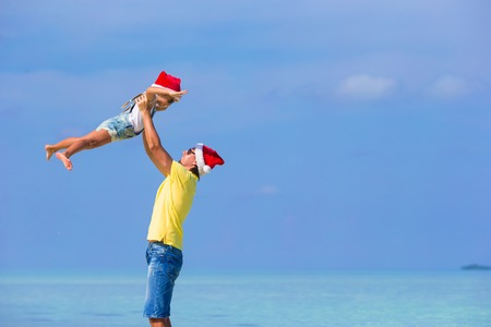 Little girl and happy dad in Santa Hats enjoy beach vacation photo