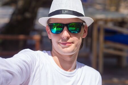 boasting: Young man making his selfie on beach at outdorr cafe