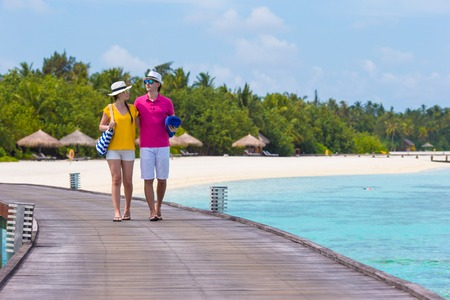 Young couple on beach jetty at tropical island in honeymoon Stock Photo