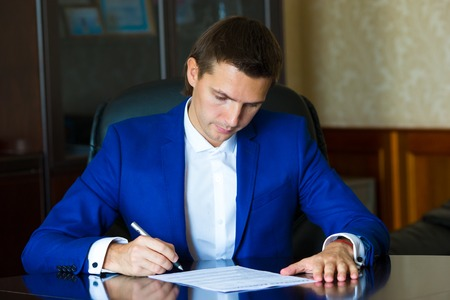businessman pondering documents: Business man signing a contract in big office