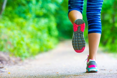 Close-up on shoe of athlete runner woman feet running on road Standard-Bild