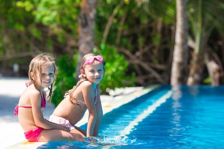 black baby girl: Adorable little girls playing in outdoor swimming pool Stock Photo