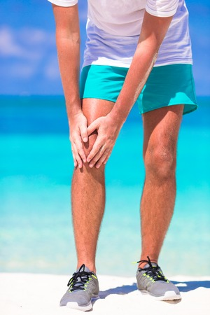 excruciating: Male athlete suffering from pain in leg while exercising on white beach