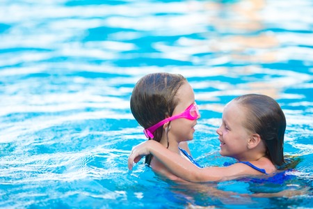 kids swimming: Adorable little girls playing in outdoor swimming pool Stock Photo