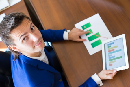 businessman working at his computer: Young businessman working with tablet computer, documents and graphs in his office