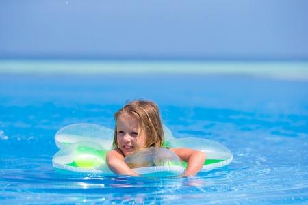 children swimsuit: Little happy adorable girl in outdoor swimming pool