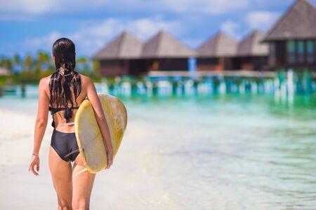 chica surf: Ni�a de surf esbelta joven en playa blanca con la tabla hawaiana amarilla Foto de archivo