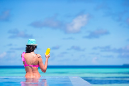 suncare: Young woman applying sun cream during beach vacation