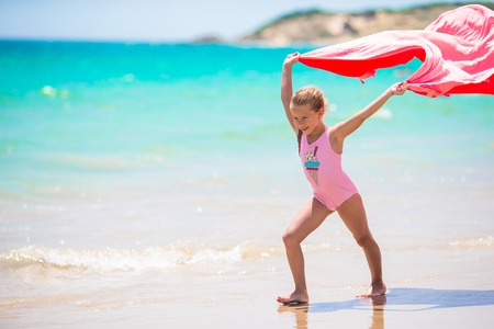toallas: Ni�a linda que se divierte corriendo con la toalla y que disfruta de vacaciones en la playa tropical con arena blanca y agua turquesa del oc�ano