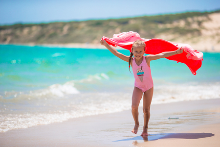 girl with towel: Cute little girl having fun running with towel and enjoying vacation on tropical beach with white sand and turquoise ocean water