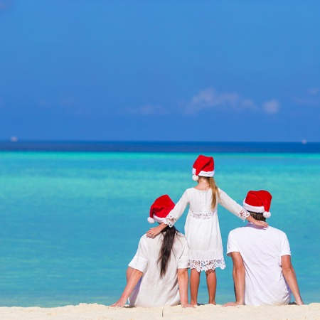guy on beach: Happy family of three in Santa Hats during tropical vacation