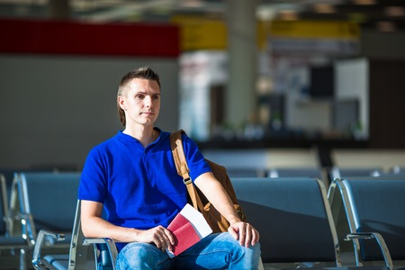 emigration: Closeup of man holding passports and boarding pass at airport Stock Photo