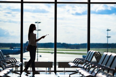 waiting girl: Silhouette of passenger in an airport lounge waiting for flight aircraft