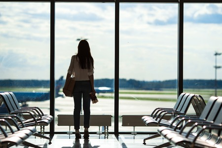 plane landing: Silhouette of passenger in an airport lounge waiting for flight aircraft