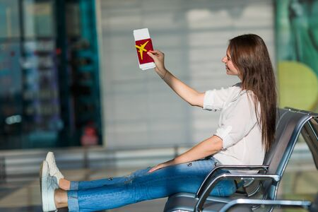 air ticket: Happy woman with air ticket at airport waiting for flight Stock Photo