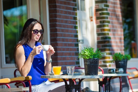 tomando jugo: Beautiful woman sitting in outdoors cafe in european city eating breakfast and drinking juice