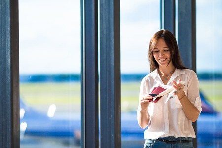 model airplane: Happy woman with small model airplane inside airport