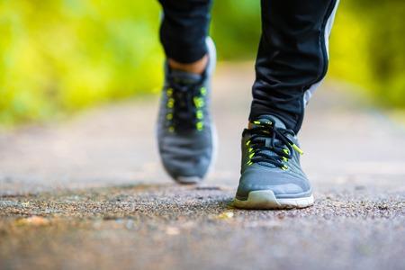 Closeup on shoe of athlete runner man feet running on road