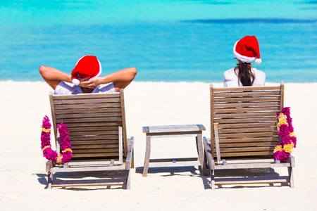 man with hat: couple in Santa hats relaxing on tropical beach during Christmas vacation Stock Photo