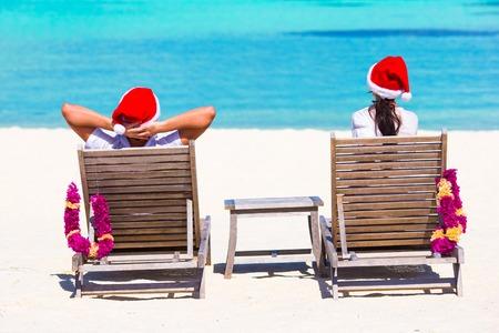 hombre con sombrero: pareja en los sombreros de Santa se relaja en la playa tropical durante las vacaciones de Navidad
