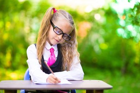 schoolgirl uniform: Happy little schoolgirl with notes and pencils going back to school outdoor