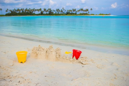 sandcastle: Sandcastle at white beach with plastic kids toys background the sea