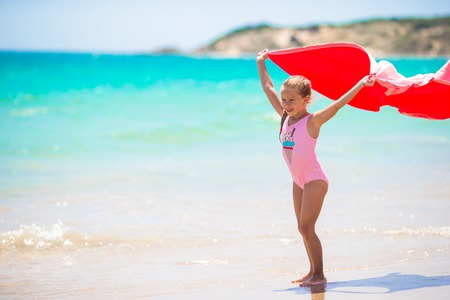 little girl swimsuit: Cute little girl having fun running with towel and enjoying vacation on tropical beach with white sand and turquoise ocean water