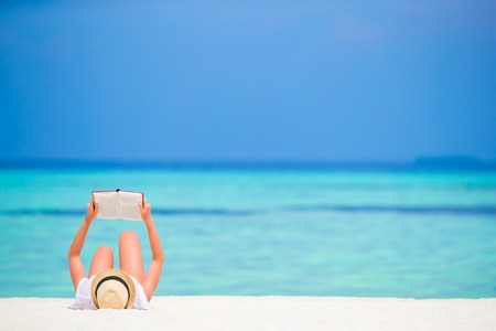 Young girl reading on tropical white beach Banco de Imagens