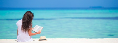 Young girl reading on tropical white beach Stock Photo