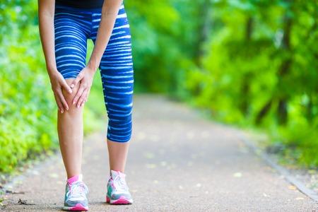 pain: Atleta de sexo femenino que sufren de dolor en la pierna durante el ejercicio Foto de archivo