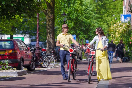 Young happy ouple on bikes in old streets in Amsterdam Stock Photo
