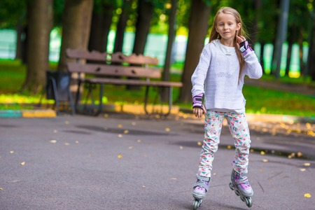 rollerskater: Roller skating happy little girl with protective gear Stock Photo