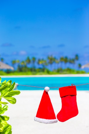 christmas stocking: Red Santa hat and Christmas stocking hanging on tropical beach