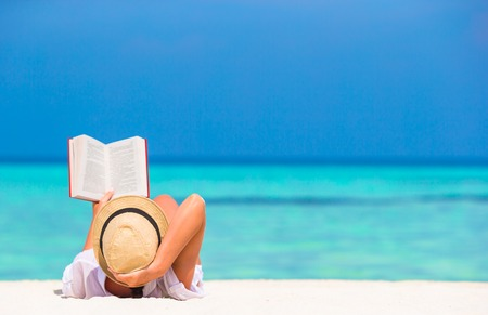 Young girl reading on tropical white beach Standard-Bild
