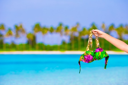 Close-up swimsuit on background of turquoise water and palmtrees