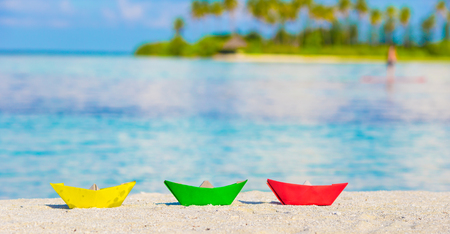 yellow paper: Colorful paper boats on tropical beach outdoors