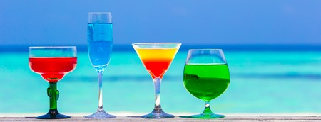 pool party: Colorful tasty cocktails background turquoise sea at exotic resort Stock Photo