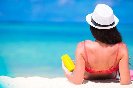 suncream: Beautiful woman holding a suncream lying on a tropical beach