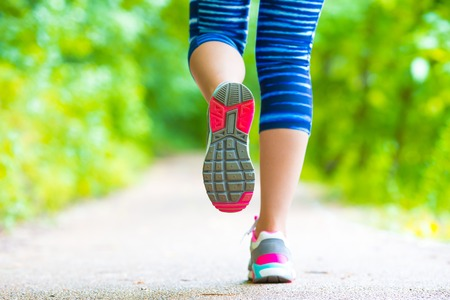 Closeup on shoe of athlete runner woman feet running on road