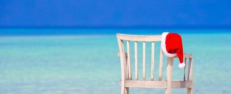 Red santa hat on chair longue at tropical caribbean beach Stock Photo
