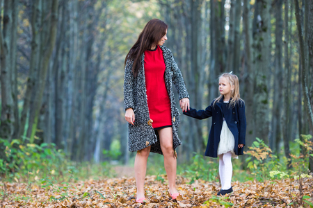Portrait of cute girl and happy mother in yellow autumn forest on a warm sunny day Stock Photo