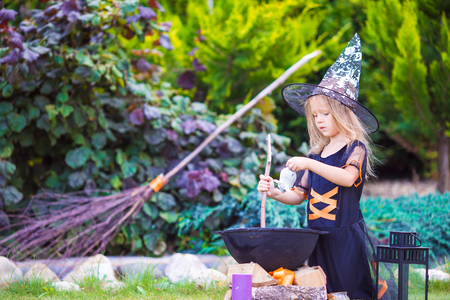 witch: Happy girl in halloween costume with jack pumpkin.Trick or treat