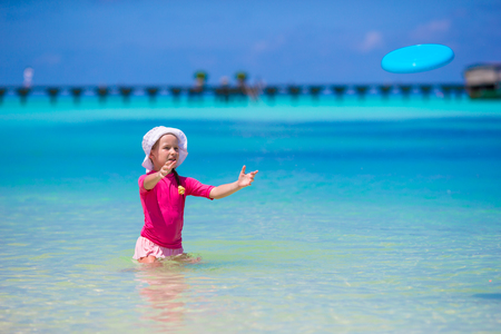 little girl swimsuit: Little girl playing  on a tropical white beach